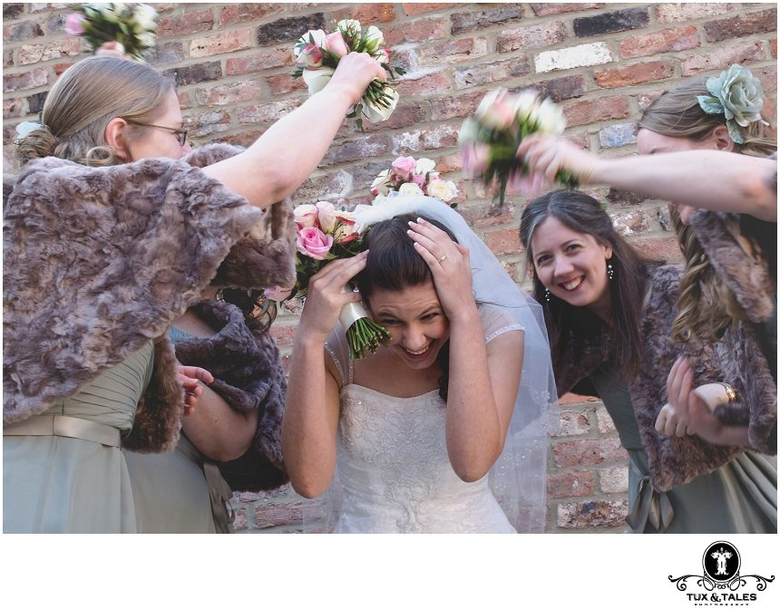 Funny bridesmaids photo with bridesmaids hitting bride with bouquet