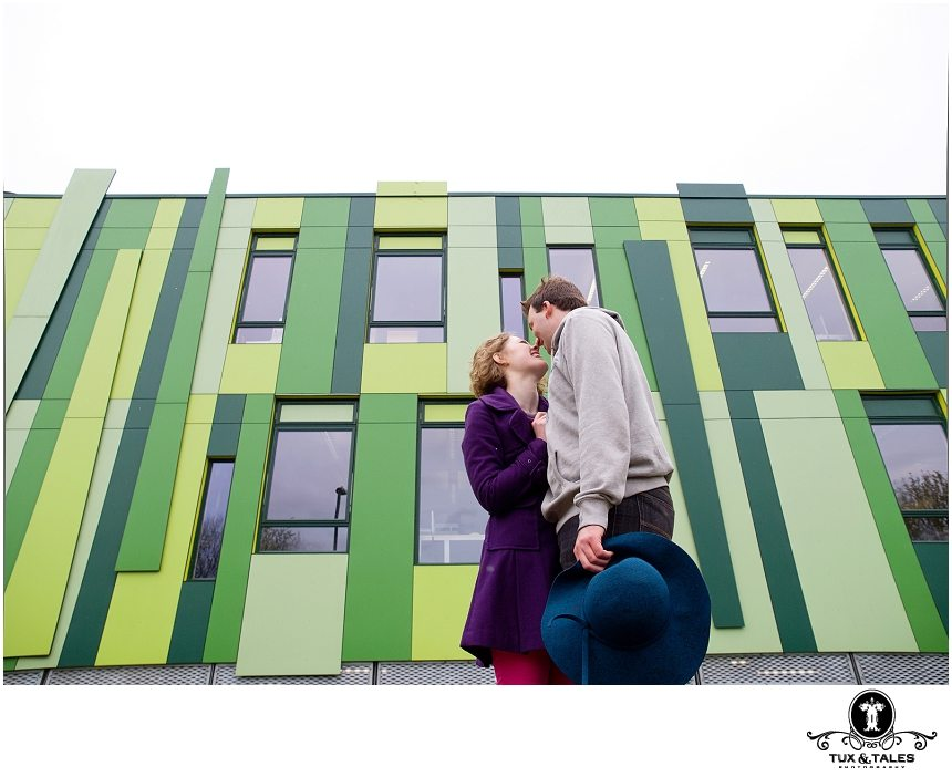 A couple have engagement photos taken outside of a green building