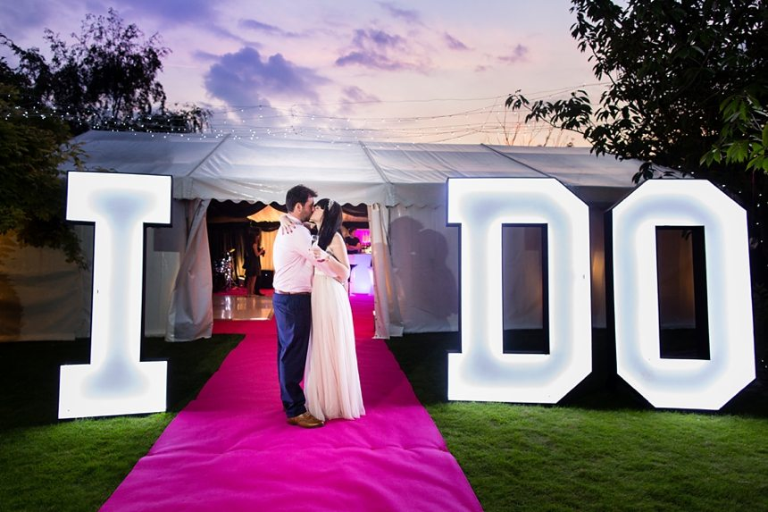 "Bride & Groom kissing in front of light up ""I DO"" letters with cherise carpet & sunset"