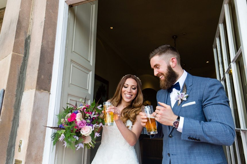 groom smiling with bride holding drinks and bouquet walking out of door