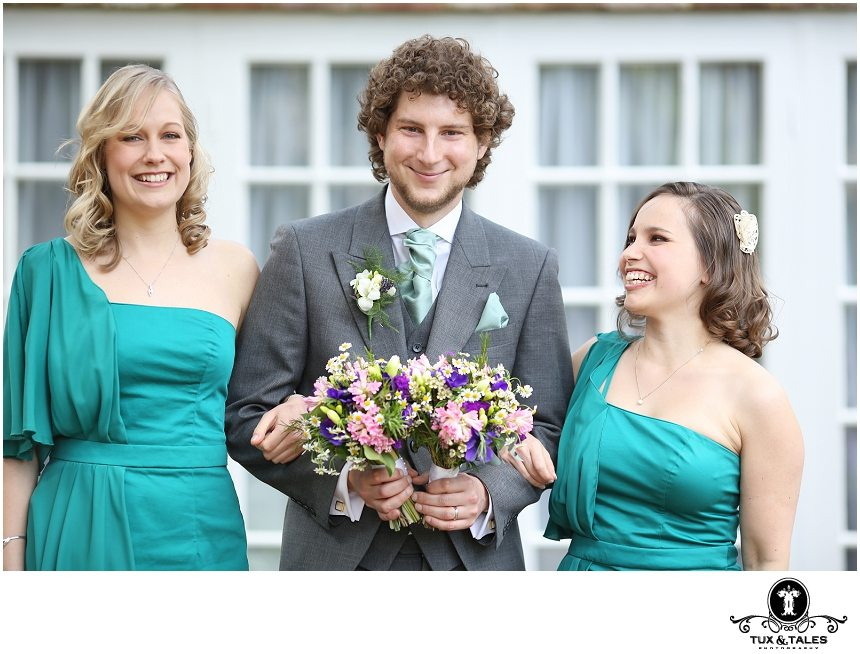 A groom holds the bouquets for the bridesmaids at Powder Mills Hotel in Sussex