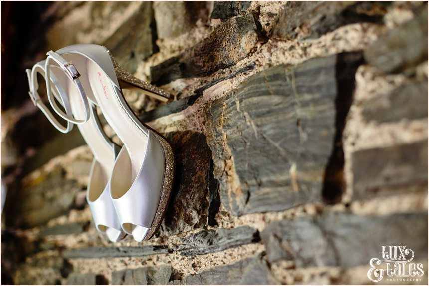 Shoes hang from a stone wall at Lake district wedding New House Farm