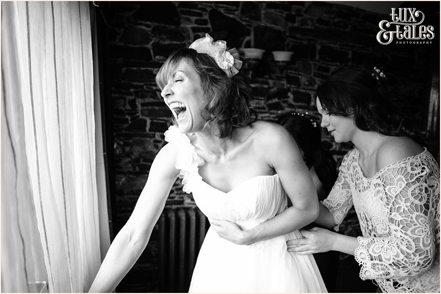 Bride laughs as they close up her wedding dress at New House Farm in the Lake District