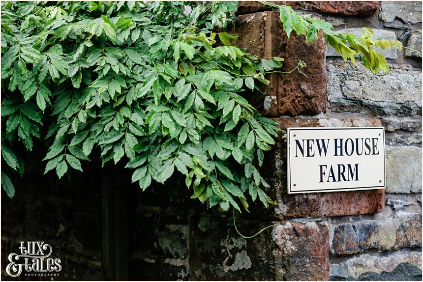 Sign saying New House Farm next to some ivy on a stone wall