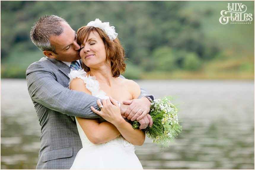 Groom kisses bride at lake buttermere wedding