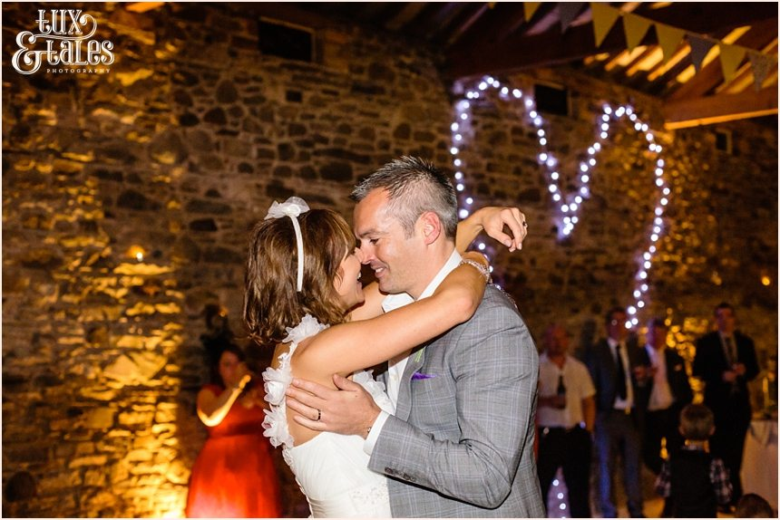 Bride and groom during first dance with heart shaped fiary lights int he background