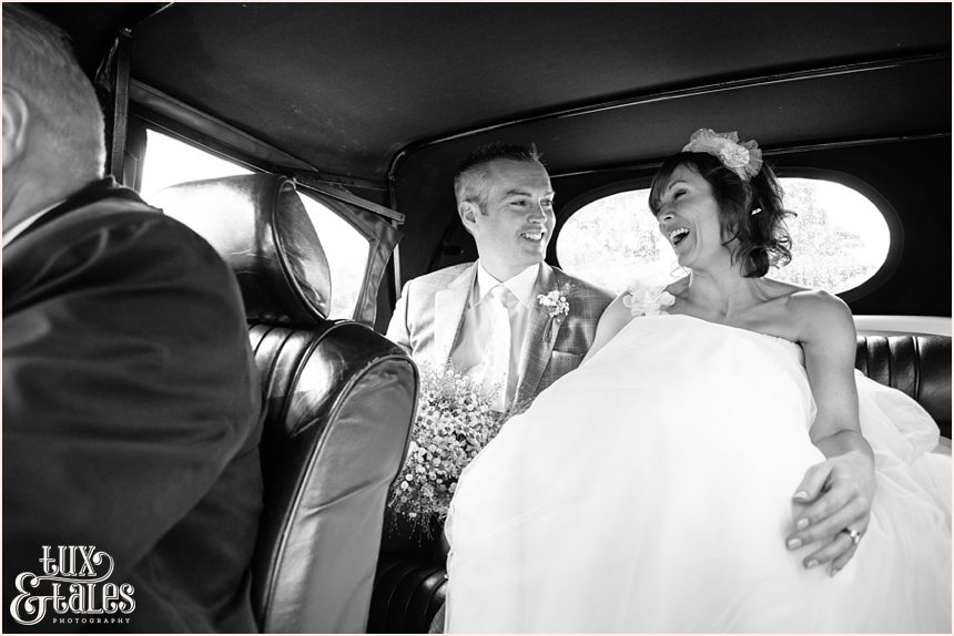bride and groom riding in vintage car in the lake district