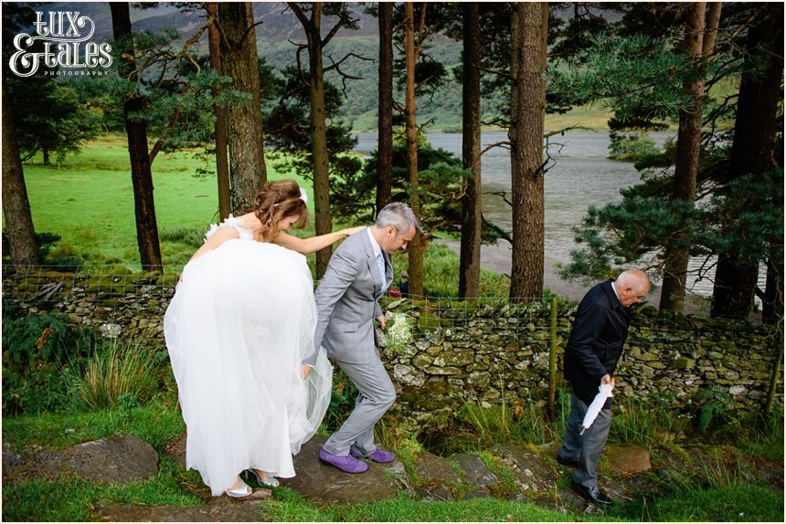 Bride, groom and chauffeur walking down the mountain at lake buttermere