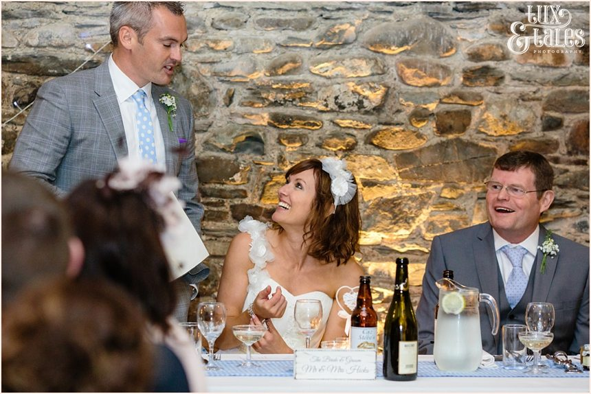 Bride smiles at groom during wedding speech