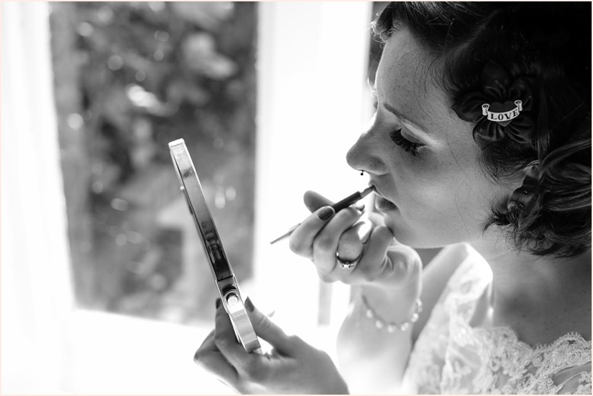 Bridal preparation wedding photography with bride applying lipstick in mirror