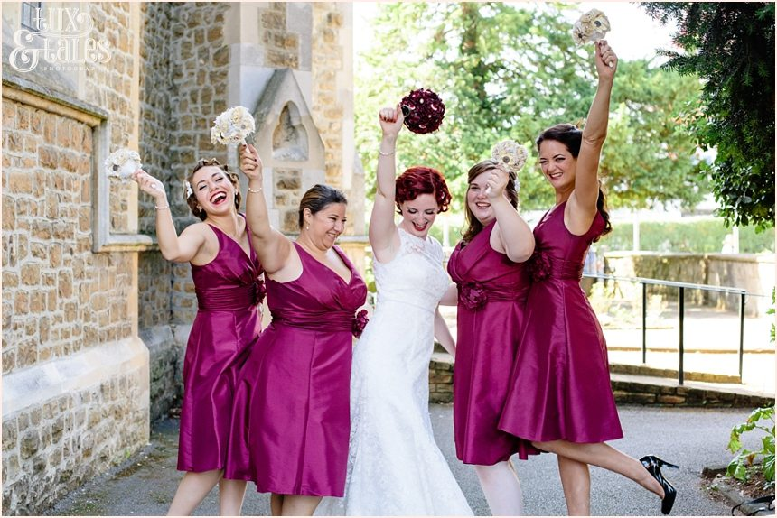 Red headed tattoo bride holds fabric bouquet in air with bridesmaids wearinf red