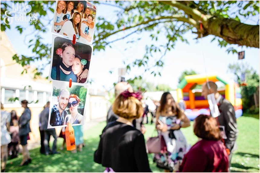 Photographs hanging from trees at wedding