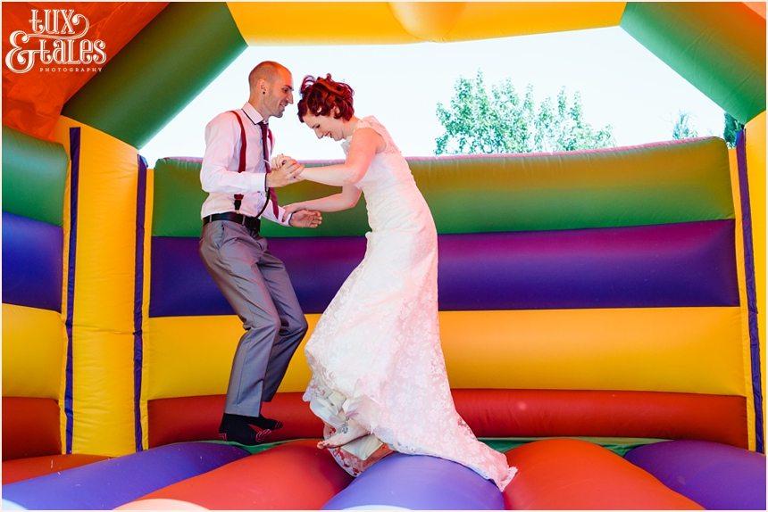 bride & groom bounce in a bouncy castle