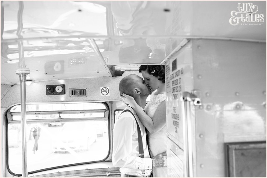 Bride and groom kiss on the stairs of lonson wedding bus