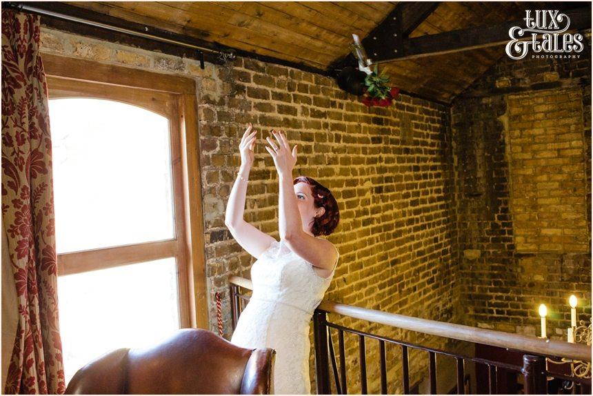 Bride throws a bouquet over a balcony at London wedding
