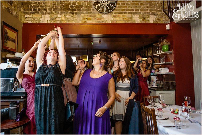 Women catch bouquet at London wedding Inn at Kew Gardens