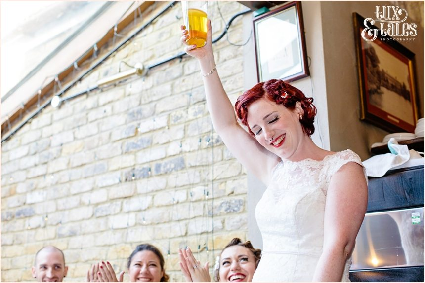 Bride holds up a pint in her speech at tattoo wedding red and black details