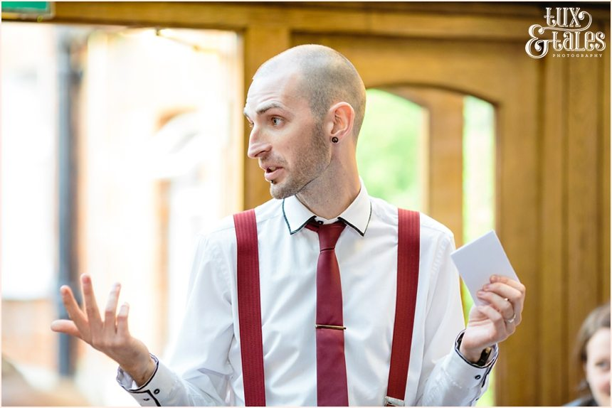 Groom wearing red braces gives speech