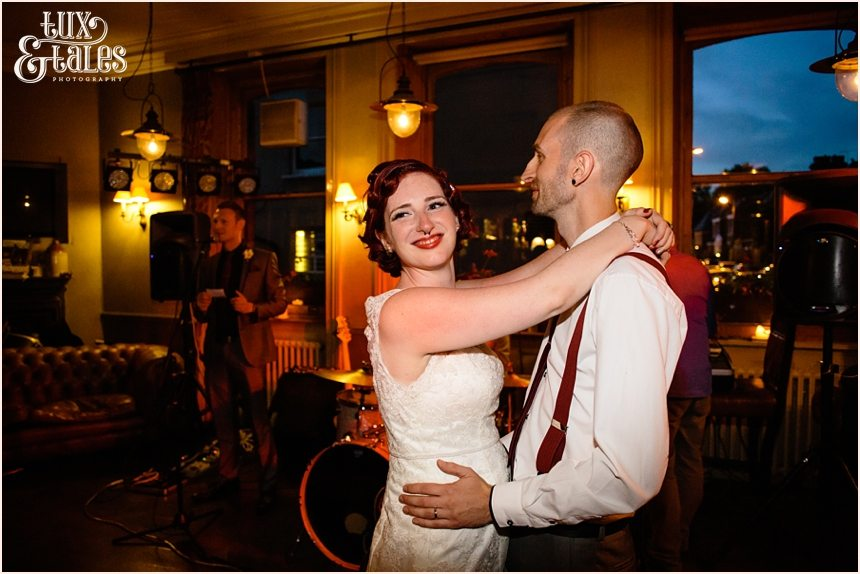 redheaded bride dances with alternative styled groom