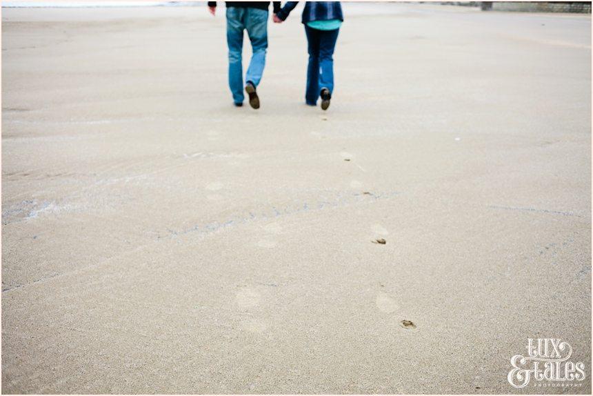 couple leaving footprints int he sand on beach