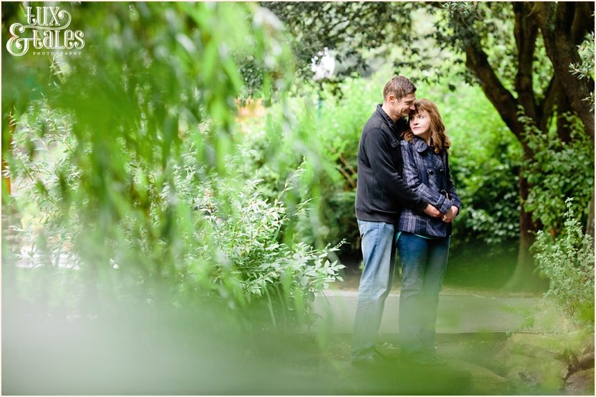 Engaged couple cuddle behind trees in Scarborough