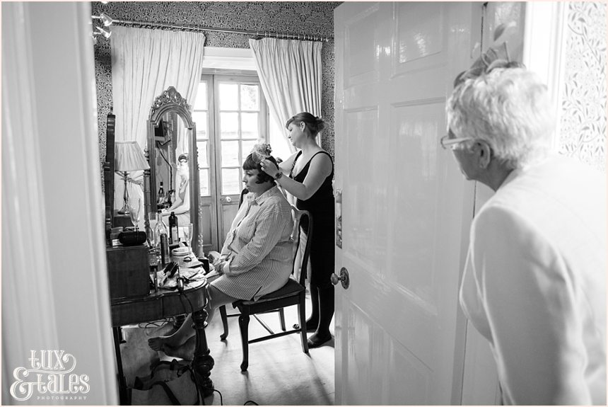 Brides mother looks on has bride has hairpiece put on at vintage wedding in yorkshire