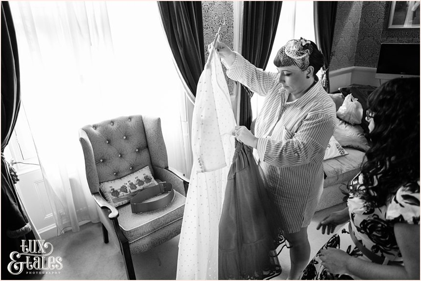 Bride looks at courutre company dress before she puts it on at vintage themed wedding in Yorkshire