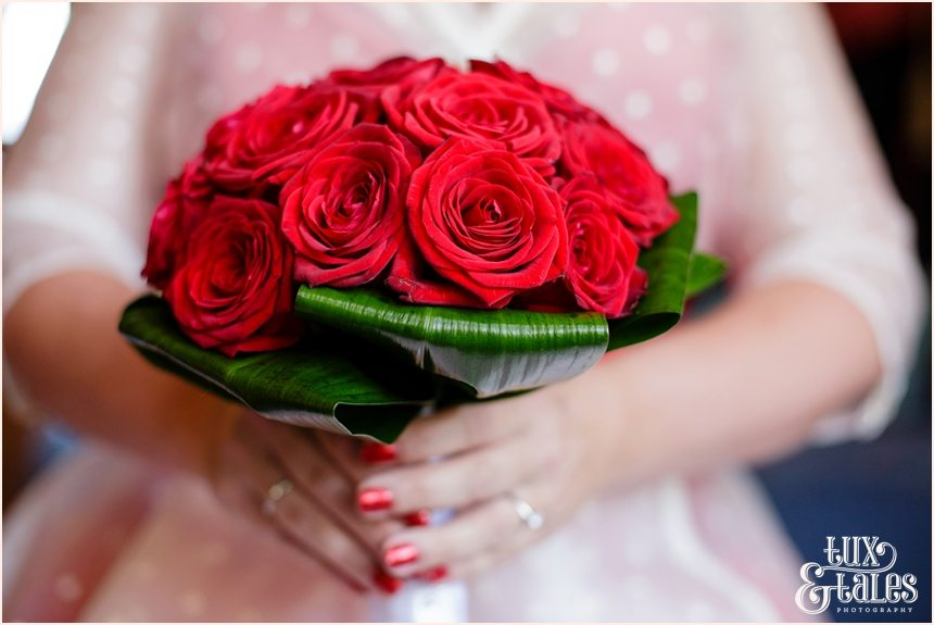 red rose bouquet bride with red sparkle nail polish