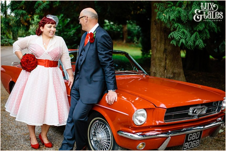Bride and groom pose in front of vintage car