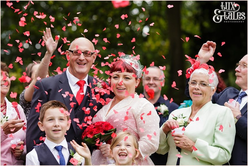 Couple showered inr ed heart confetti at vintage themed wedding in Yorkshire