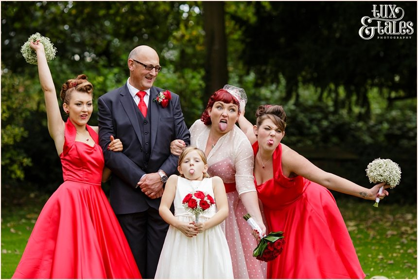 Bride, groom and daughters make funny faces at red themed vintage wedding in Yorkshire