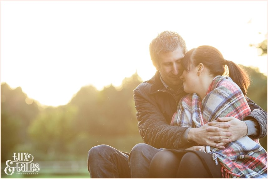 couple wrapped in tartan rug at elvaston castle engagement photo session in autumn