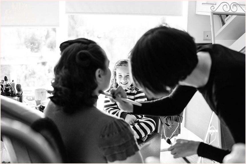 Flower girl watches as bride has makeup applied by Vicky Farr