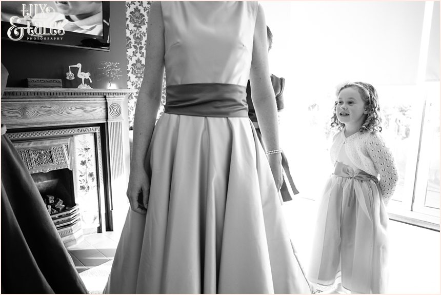 Little girl watches as bride gets her dress on at Swanland Wedding