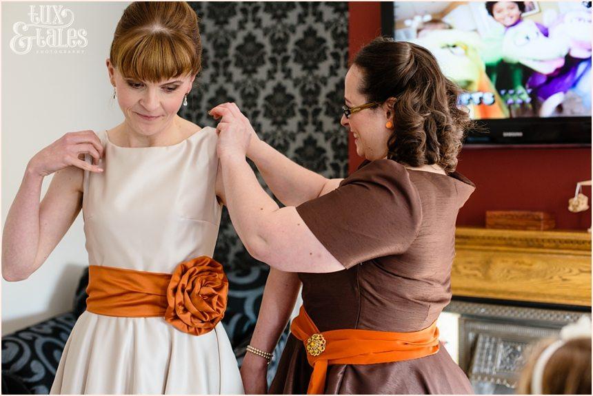 Bride puts on golden coloured wedding dress