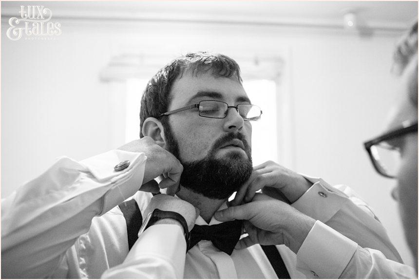 Groom puts on bow tie at York Wedding