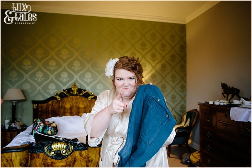 Bride makes silly face holding trousers at Grays Court wedding in York