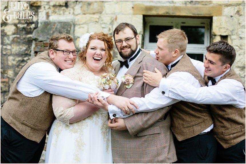 Groomsmen give big group hug at York wedding