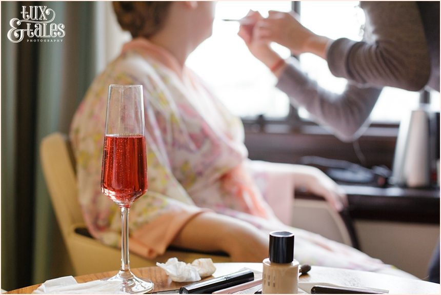 Cedar Court Grand Wedding bride gets makeup applied inw indow with pink champaign