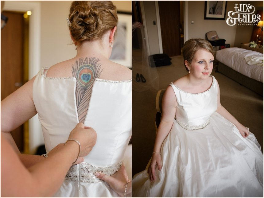 Bride with peackcock feather tattoo down her back is zipped into her wedding dress at York wedding in Cedar Court Grand Hotel