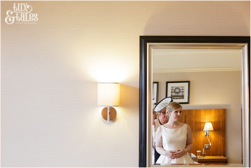 Bride looks in mirror at Cedar Court Grand Hotel Wedding