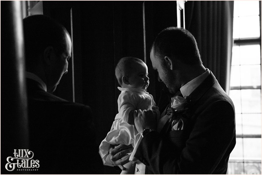 Groom holds baby at York wedding