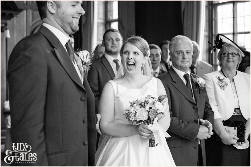 Bride smiles and laughs as  she sees groom at York wedding