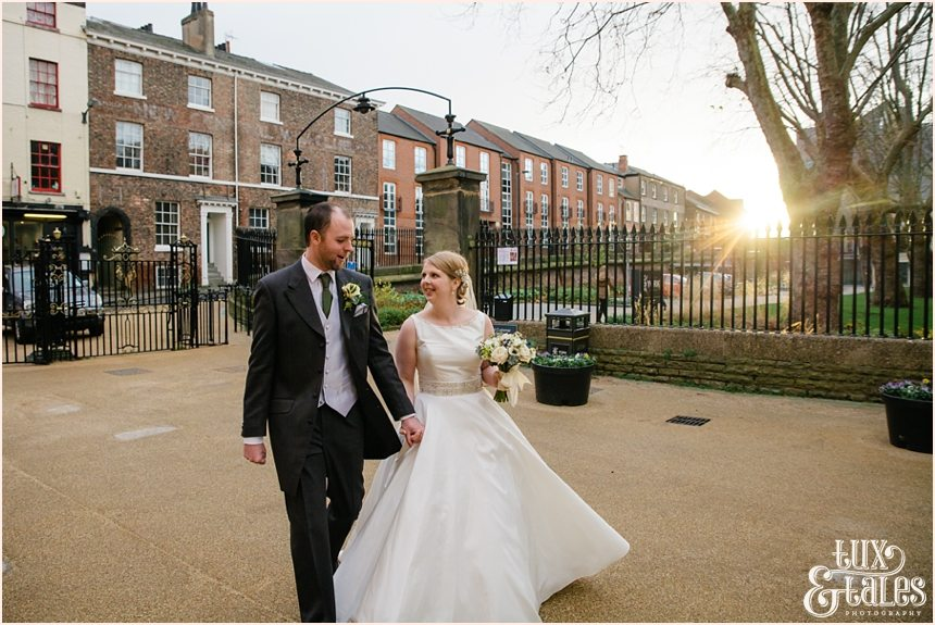 Bride and groom walk in York with the low winter light behind them. they are relaxed and smiling