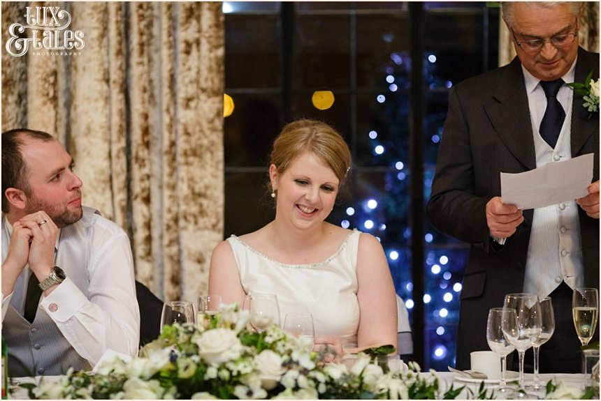 Bride smiles during speeches at York wedding