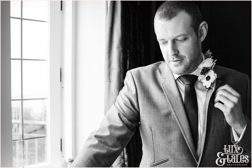 Groom adjusting buttonhole at hogarths hotel wedding