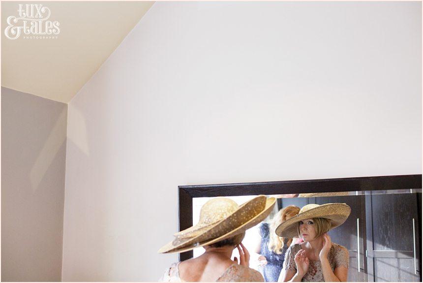 Bride adjusts hat in mirror at hogarths hotel wedding