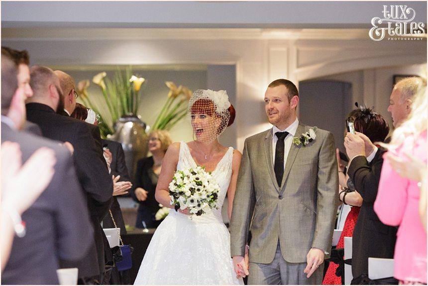 Bride and groom walk back up aisle at hogarths hotel