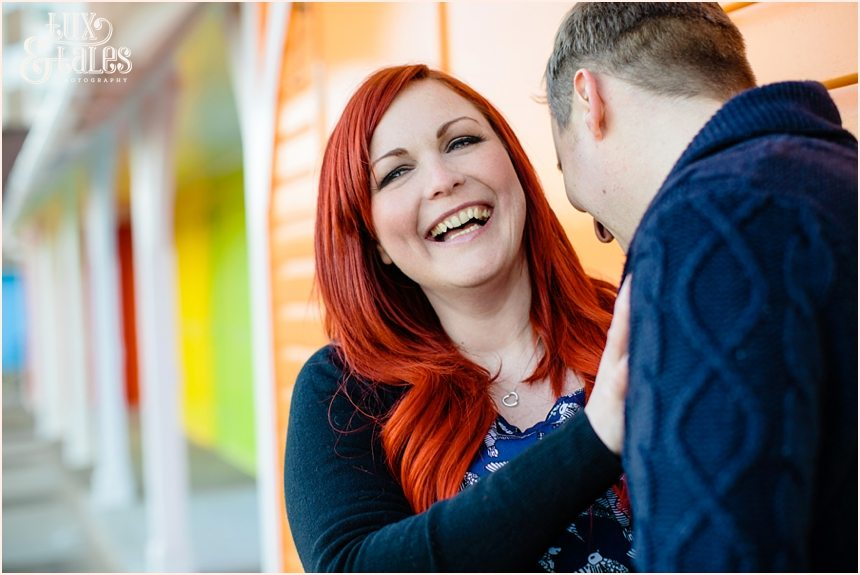 A cute couple laughs at each other ine Scarborough at engagement shoot