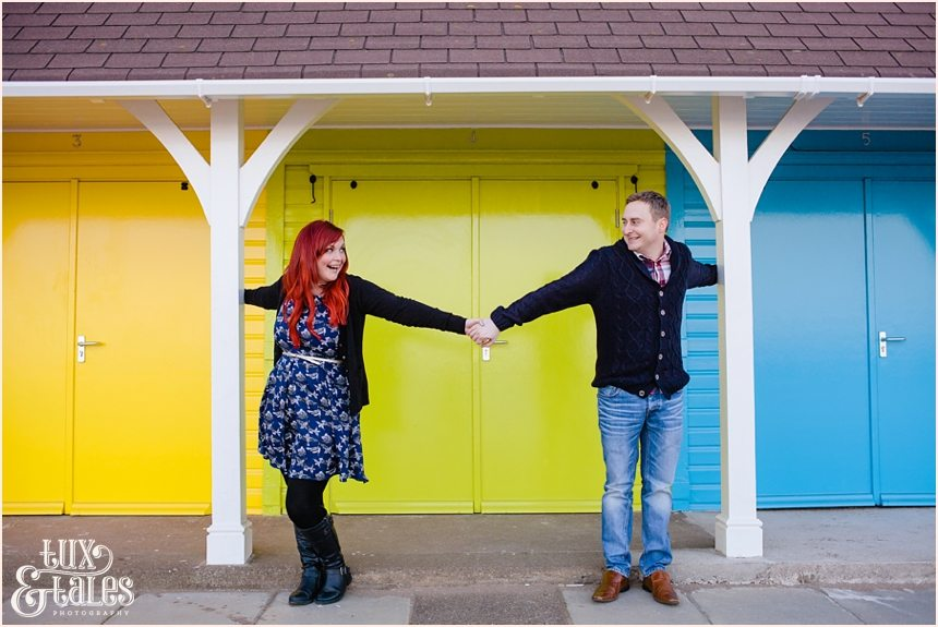 couple holding hands in front of rainbow coloured beach huts
